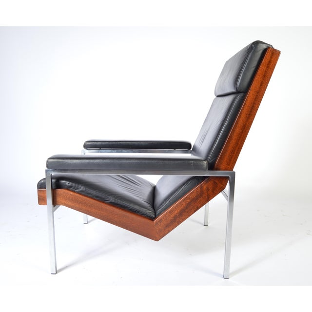 Coated Flex cable suspension, a solid walnut frame with stainless steel legs having smooth black leather with cushion...