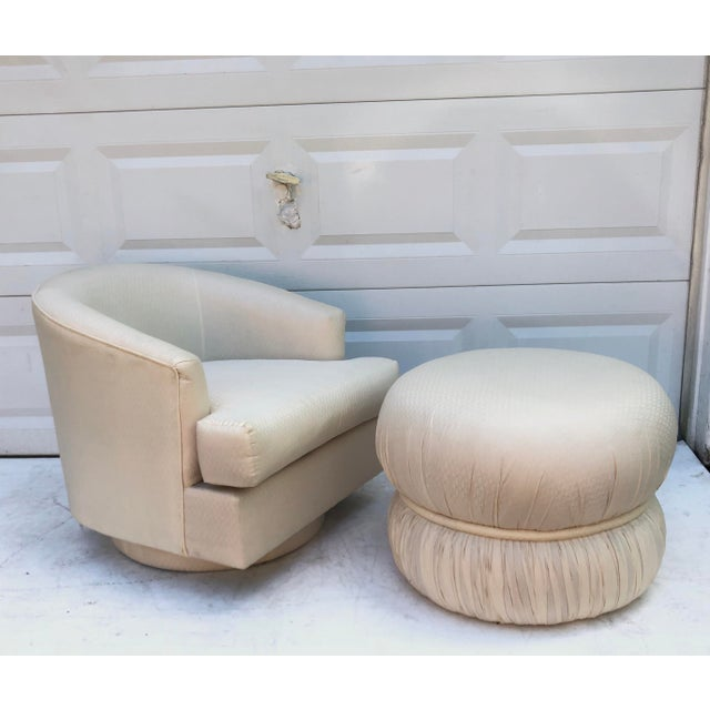 This modern club chair is covered in textured white upholstery with matching pouf ottoman and comfortable seat...