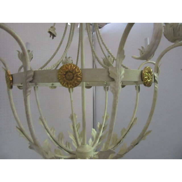 Charming large white bird cage chandelier with 8 lights. There are large brass rosettes going around the chandelier....