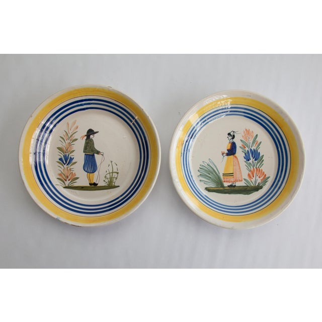 A charming pair of antique early 20th-Century French faience Henriot Quimper plates. Maker's mark on reverse. These...