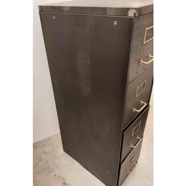Four drawer stripped steel filing cabinet with original brass handles and card holders.