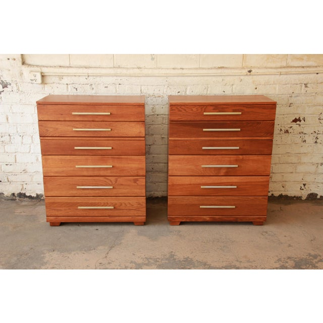 Offering an exceptional pair of Mid-Century Modern solid oak highboy dressers by iconic designer Raymond Loewy for Mengel...