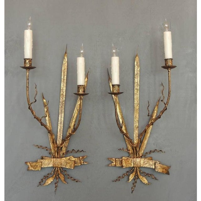 A pair of tall gilt tole sconces made in Spain in the early-20th century, circa 1920, featuring two candles with gilded...