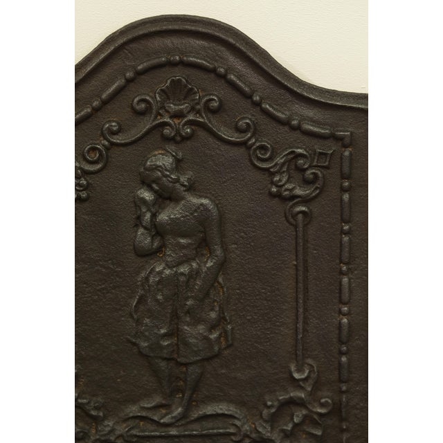 """Nice small and very decorative antique cast iron fireback displaying a """"weeping women"""". This fireback is in excellent..."""