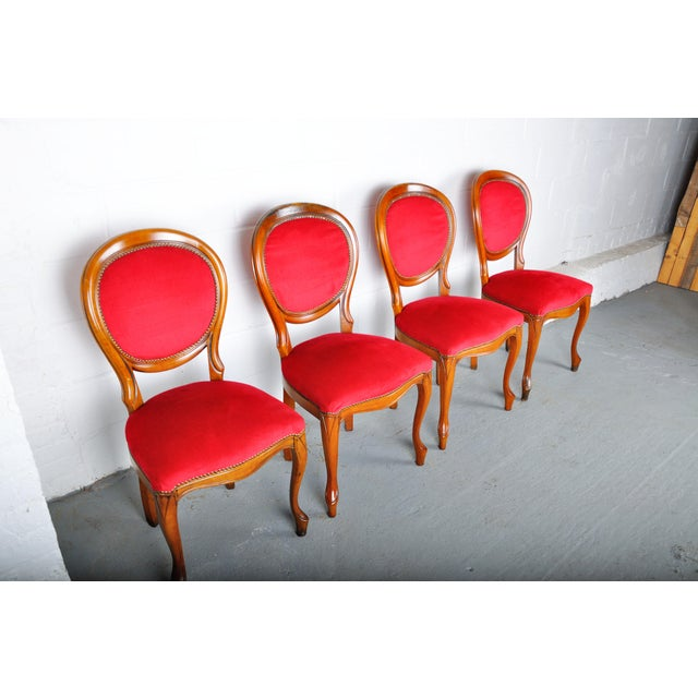 Set of 4 vintage Louis XV dining chairs made of solid maple wood. The chairs come with their original red velvet...