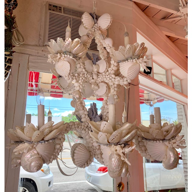 Stunning white chandelier for over a dining table or in a high foyer. All white except a few pops of blue. Two-tiered,...