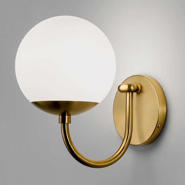 A brushed brass wall light with a single arm with a satin opal glass globe. The glass has an integral threaded metal...