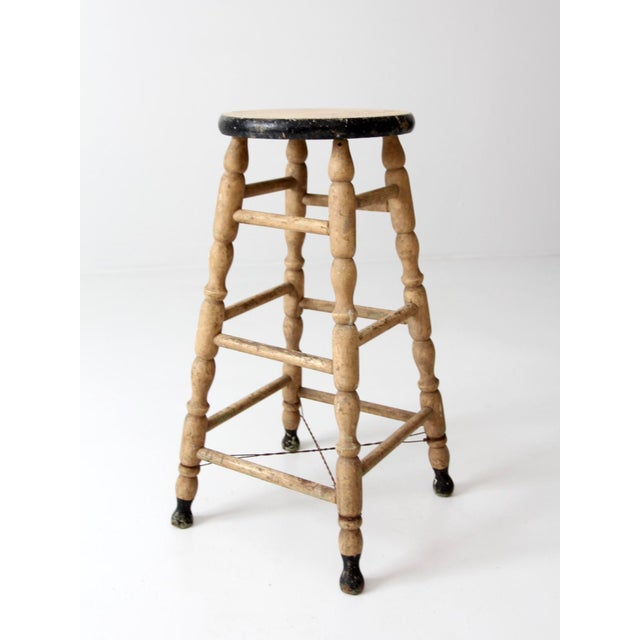 This is an antique turned wood stool circa late 19th century. The tall wooden farmhouse stool features cream and black...