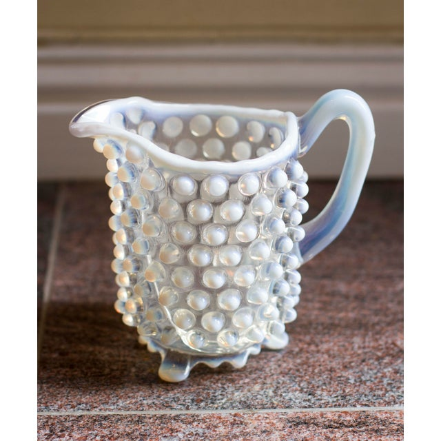 A lovely vintage small hobnail pitcher, featuring a blue and white hue. The pitcher is in overall good condition but there...