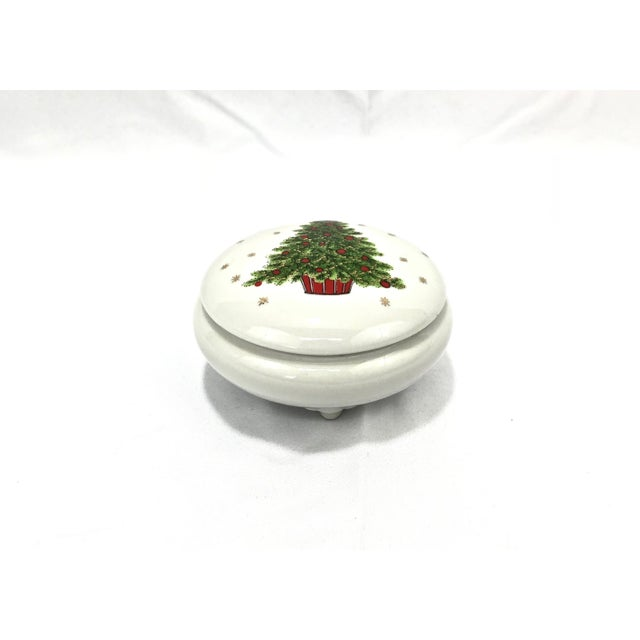 Here is a very dainty little footed porcelain box depicting a Christmas tree in a red box with shimmery gold stars all...