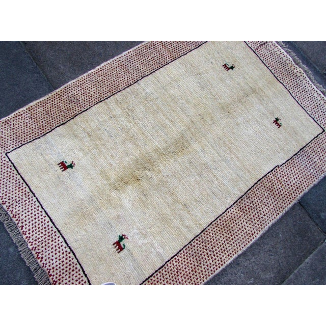 Handmade vintage Persian Gabbeh rug in cream beige wool with red border. The rug is from the end of 20th century in...