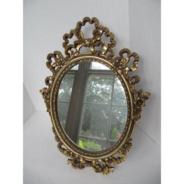 Beautiful, ornate, gold Syroco Wood mirror with ribbons, bows and flower details. This mirror can be used on a vanity,...