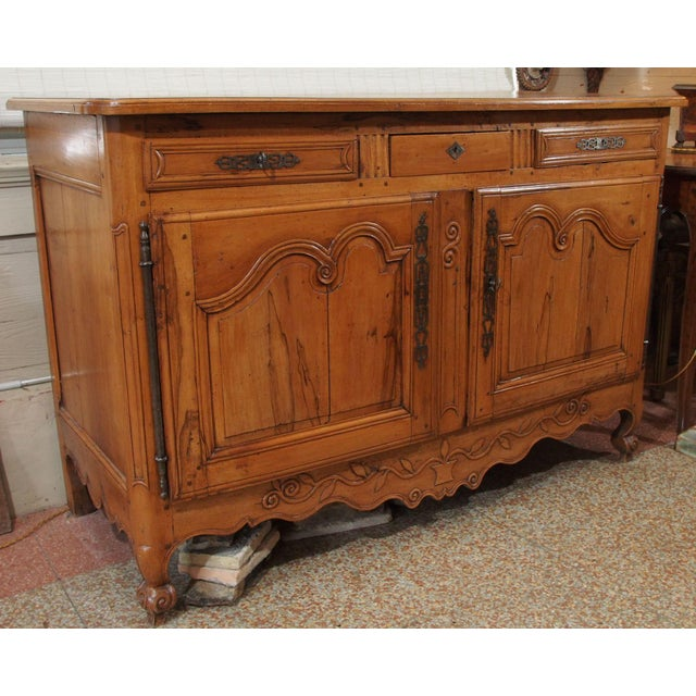 This beautiful warmly colored buffet has 3 drawers over 2 carved doors with inside shelving. Louis XV style from Provence....