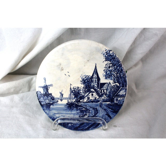 Cobalt blue and antique white Delft trivet of a Dutch harbor and church scene.