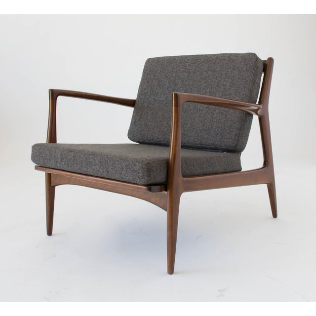 Danish Modern lounge chair in walnut-stained beech designed by Ib Kofod-Larsen for Selig. The chair has slightly curved...