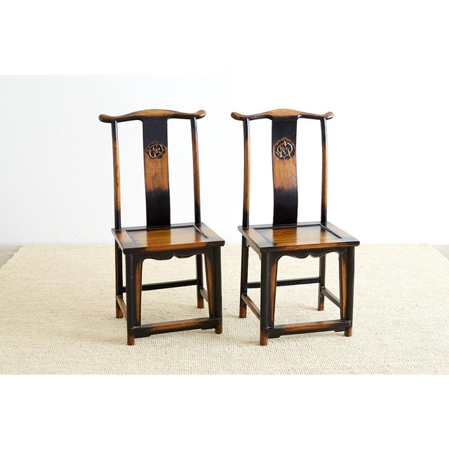 Stunning pair of Chinese yoke back officials hat chairs featuring a carved dragon motif backsplat. These carved chairs...