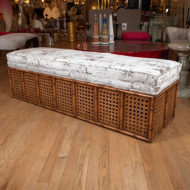 Rectangular caned wood bench with upholstered seat.