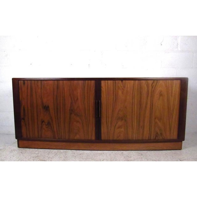 This Mid-Century rosewood tambour sideboard makes a beautiful storage piece for any room. Felt lined center drawers...