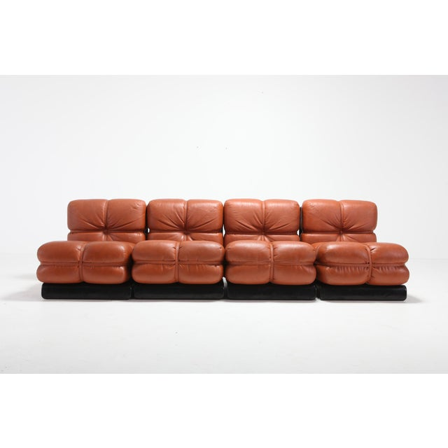 Cognac leather sectional sofa with black lacquered wooden frame by Carla Venosta. The piece consists out of 4 lounge...