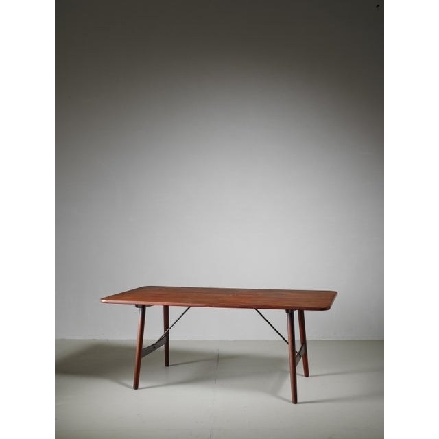 A dining table in wood with brass bars by Børge Mogensen. The top is made of teak and the legs are made of oak. Mogensen...