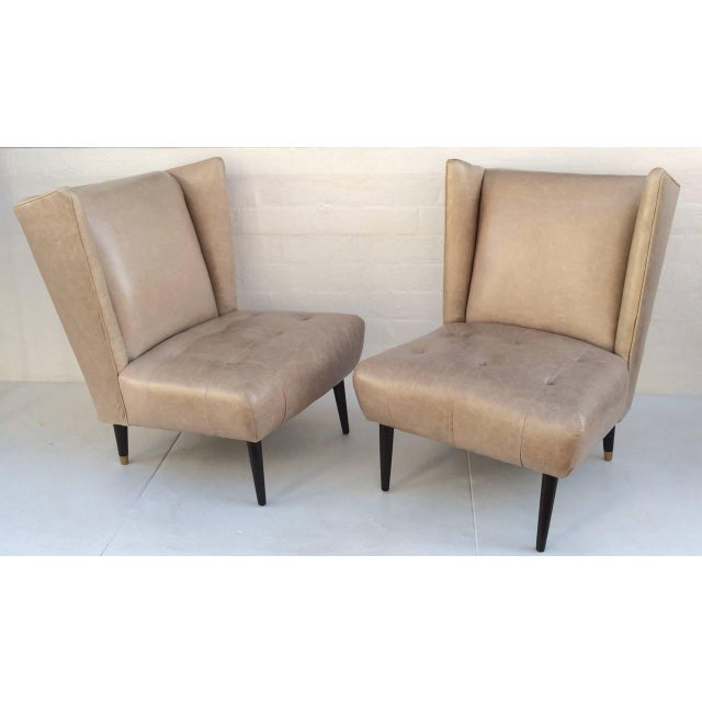 A pair of 1950s club chairs newly reupholster in a cream distressed leather, with wood tapered legs finished is a dark...