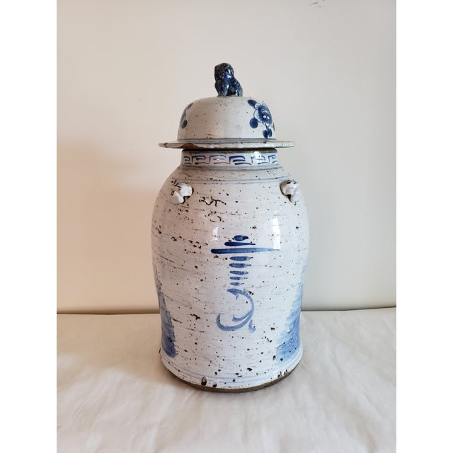 Blue and white temple jar with handpainted decorations and foo dog handle on lid.