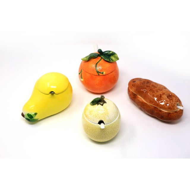 A vintage collection of condiment jars with lids and spoons, in the forms of a lemon, an orange, a pear, and a potato....