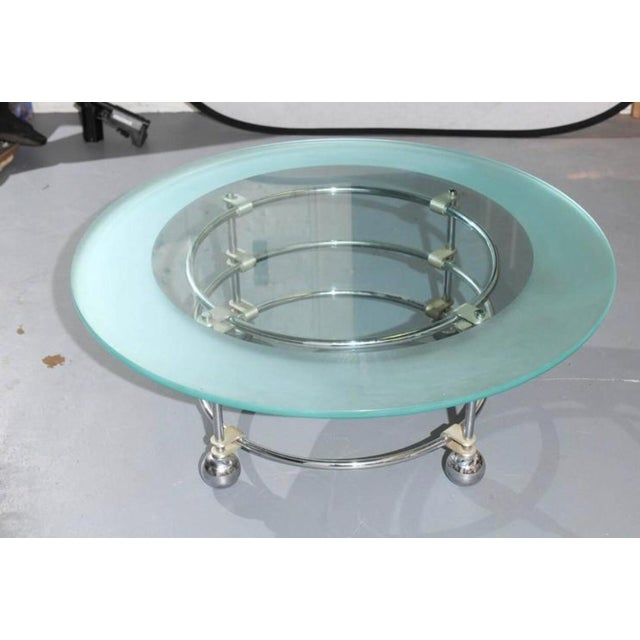 """20th Century circular coffee table having a 1/2"""" thick glass top with acid etched border resting on a chrome base with..."""
