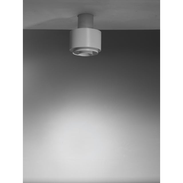 A model A2-35 white metal ceiling lamp by Paavo Tynell for Idman. The lamp is made of two cylindrical parts and a metal...