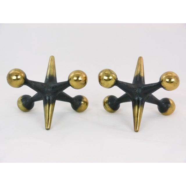"""A vintage pair of gold-tone & black cast iron jack (jax) bookends by Bill Curry. Measures: Ball to Ball +/- 7.5"""". Tip to..."""