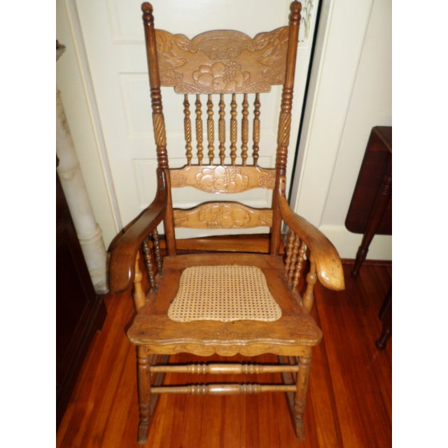 This is an Antique Ornate Golden Oak Rocking Chair that has a Gorgeous Design with Birds and Fruit with a Press design on...