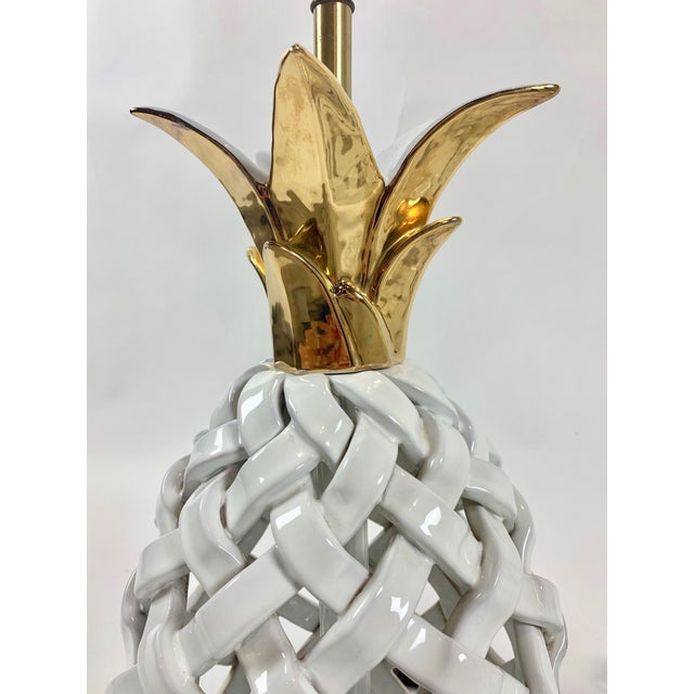A striking pair of woven ceramic pineapple form lamps with brass colored bases and metallic gold painted crowns. Lamps...