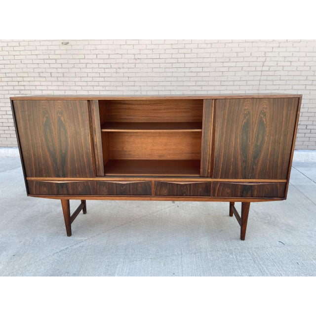 This is a Arne Vodder style rosewood highboard. Constructed of rosewood and features 3 cabinets with sliding doors on top...