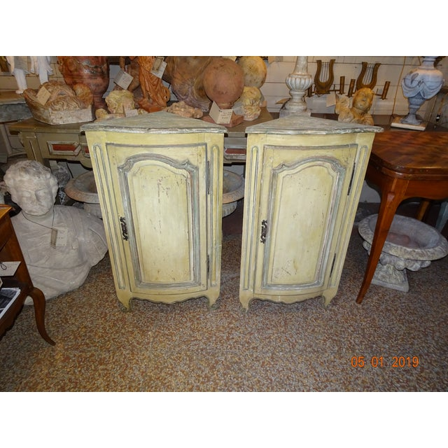 Sweet pair of 18th Century French small corner cabinets painted in different shades of green. One shelf inside. They can...