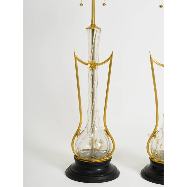 A rare pair of lamps composed of clear art glass and very precise, intricate metal work with fine detail. Professionally...