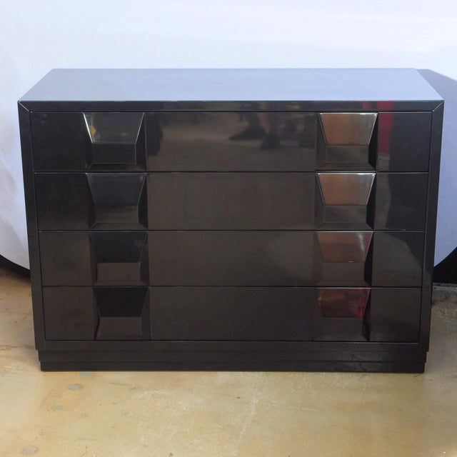 The rectangular top over bank of drawers with recessed handles, the whole in black lacquer finish.