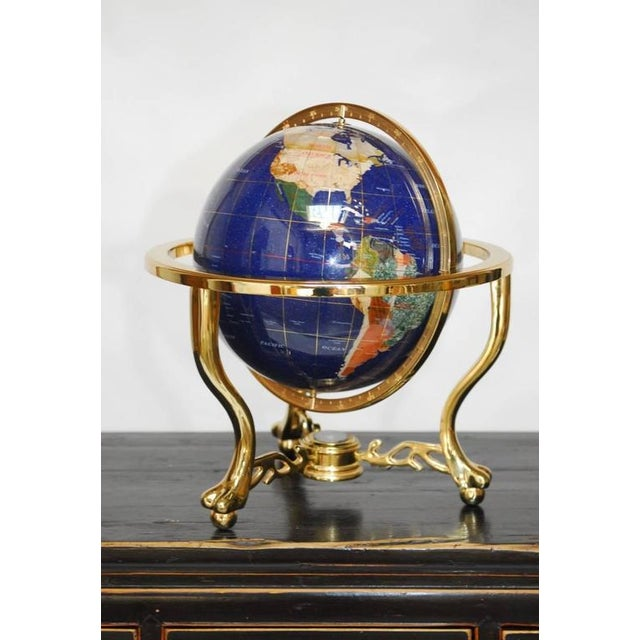 Captivating Pietra Dura globe featuring marble, mother-of-pearl and other semi-precious stones suspended in a solid brass...