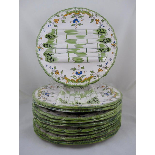 A vibrant set of ten vintage earthenware asparagus plates, beautifully hand decorated with a floral design in the faïence...