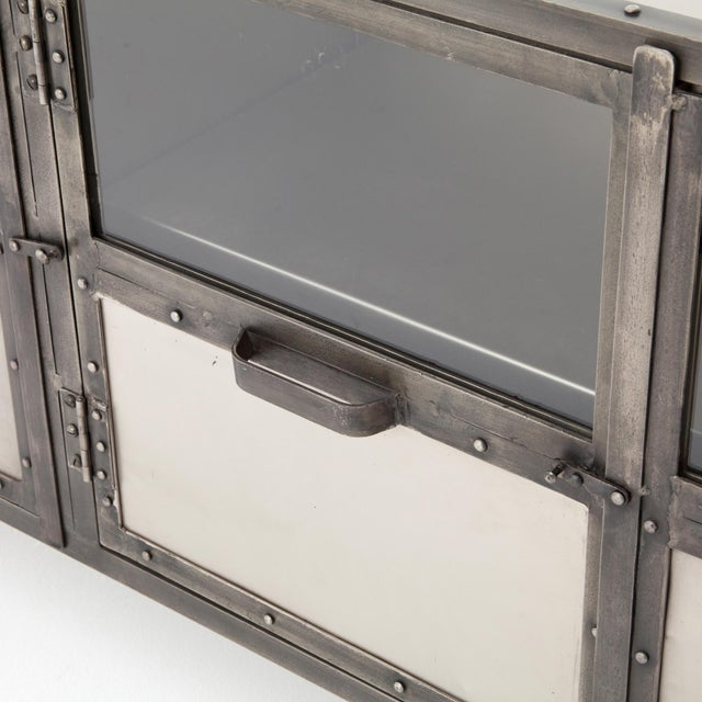 An industrial-strength console offers an intriguing home for modern media. Dark iron frame contrasts with antiqued nickel...