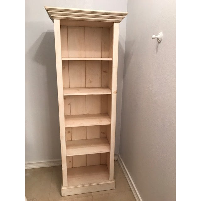 Whitewashed rustic pine bookcase with carved top. Natural wood knots and grain. Shelves are 11 inches deep. Purchased from...