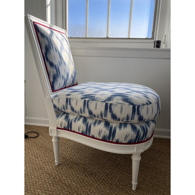 Slipper chair upholstered in a fresh, blue ikat fabric with raspberry contrast velvet welt around the base and back. White...
