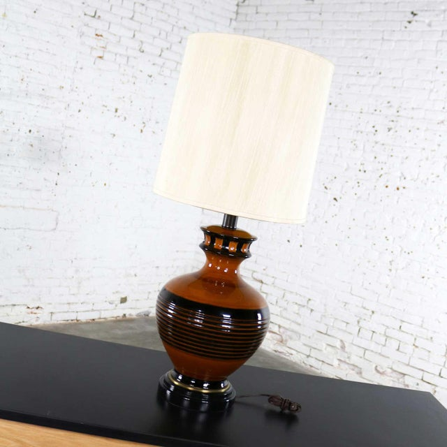 Handsome mid-century modern large brown and black bulbous ceramic lamp. It is in fabulous vintage condition. It wears its...