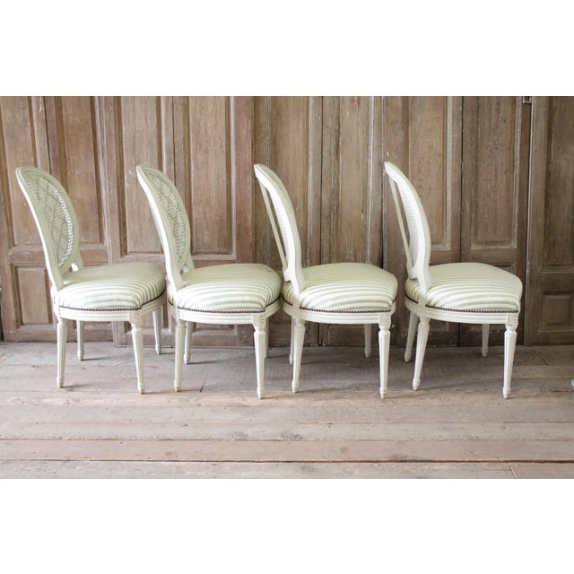 Set of four Louis XVI style French painted cane back dining chairs Original painted finish, in an off white with a pretty...
