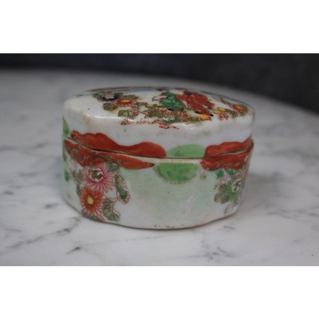Asian porcelain box, likely Japanese, of Geisha women on white and floral background. The piece is from the mid 19th century.