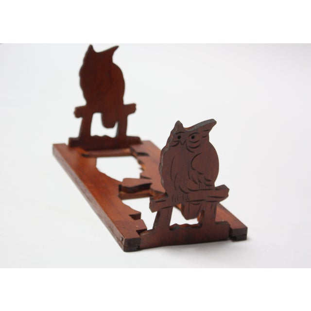 Whimsical, yet practical hand carved bookrack with owl motifs. When in use, the owls manually pop-up to create bookends....
