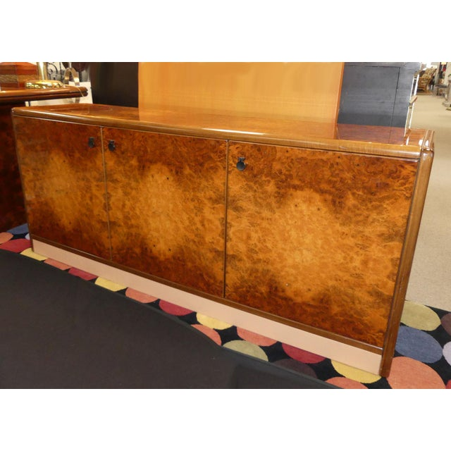 Vintage Roche Bobois lacquered burl wood credenza. Features 3 doors with 8 concealed drawers and shelves at the center....
