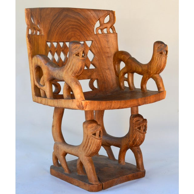 Fantastic carved sculptural Benin tribal chair, carved from a single piece of wood with four elegant lions and a carved...