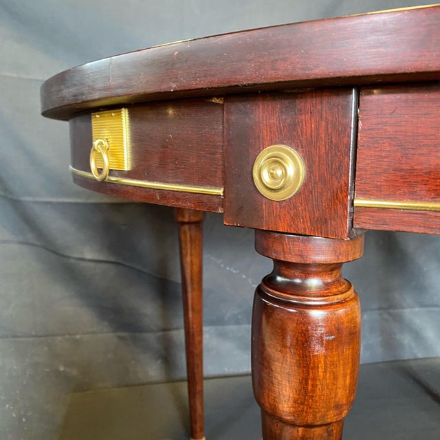 Beautiful French round mahogany and walnut table with gold accents having gold pulls on either side that extend if leaves...