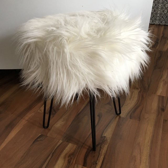 Fun vintage mid-century modern stool with black metal legs and a round, fluffy top.