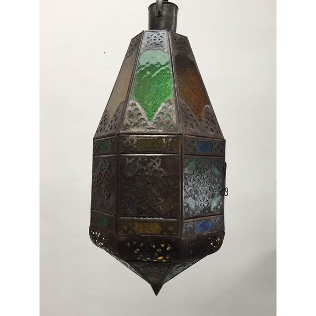 Stylish handcrafted Moroccan lantern with colored molded glass in blue, green, lavender and amber. Antique bronze finish...